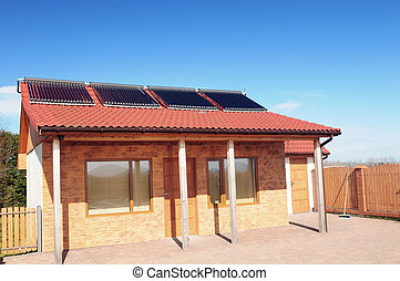 Small bungalow with solar panels on red roof under blue sky.