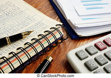 Small business accounting. Financial documents and pen on an office desk.