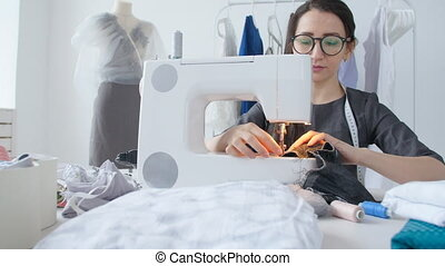 Small business and hobby concept. Young woman designer clothes working on a sewing machine in her studio