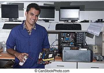 Small business: computer technician with motherboard at workshop