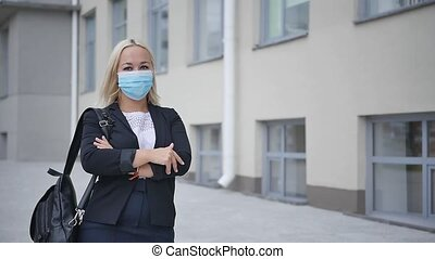 Small business during a pandemic. Business woman in a mask on a city street.