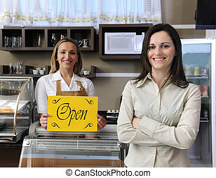 Happy owner of a caf? showing open sign - Small business:...