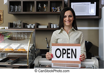 Happy owner of a caf? showing open sign - Small business: ...
