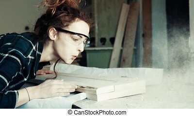 Small business of a young woman. Female worker sanding wood in the carpenter workroom. Slow motion.