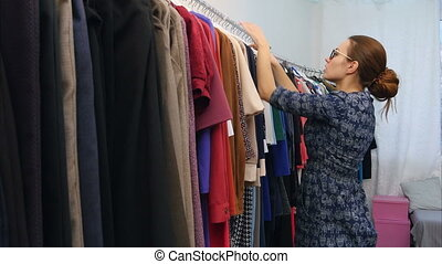 Small business owner in clothes shop checking collection....