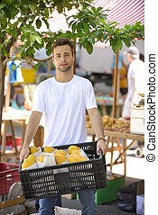Small business owner selling organic fruits and vegetables at an open street market.