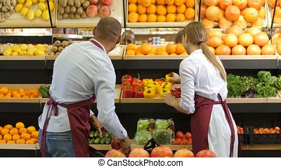 Small business owners arranging groceries at store - Multi...