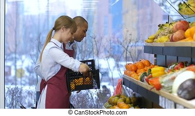Small business owners fill up fruits storage racks - Smiling...