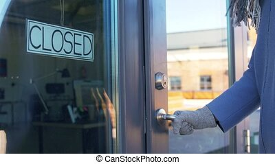 small business, pandemic and service concept - woman in glove trying to open closed office door