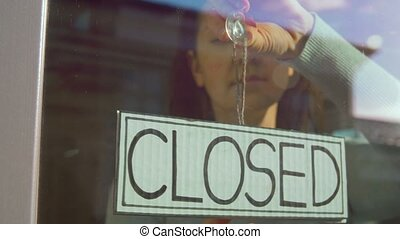 woman hanging banner with closed word on door - small ...