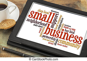 small business word cloud on a digital tablet with a cup of...