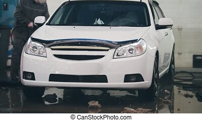 Small business - worker in auto service is washing a car in...