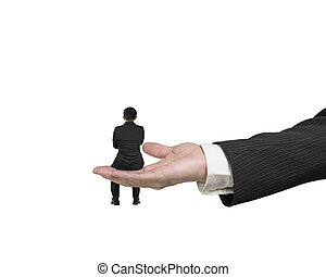 Small businessman sitting on big male hand palm
