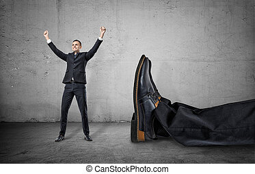 Small businessman standing with his arms up near giant leg...