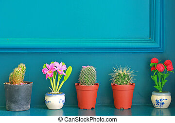 Small cactus with flower decorated on green wall