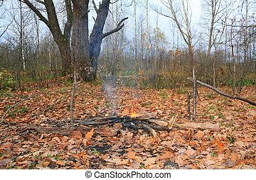 small campfire amongst yellow sheet