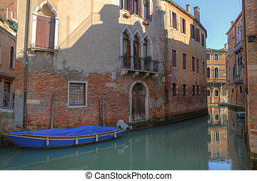 Small canal among old houses in Venice.