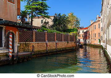 Small canal and colorful houses in Venice.