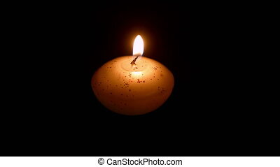 Small candle against dark background closeup