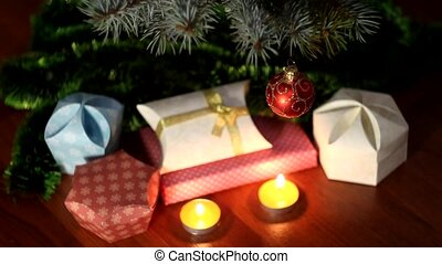 small candles near Christmas tree with gifts