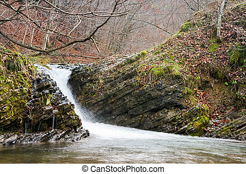 small cascade in the forest. lovely autumn scenery