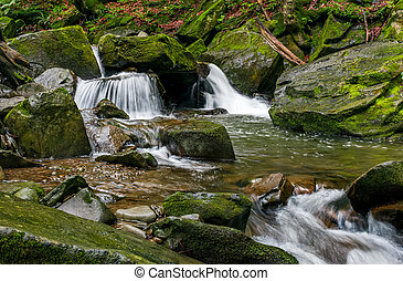 small cascade on the river among bouders in forest - small...