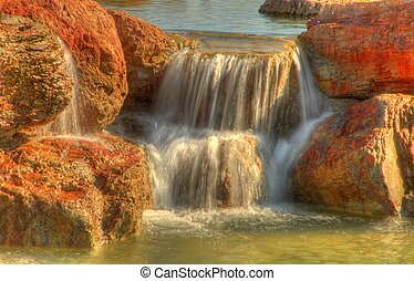 Small but quite colorful cascading waterfall flowing