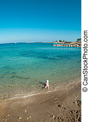 Small Caucasian child playing on sandy beach of Mediterranean sea, Cyprus. Wide angle view
