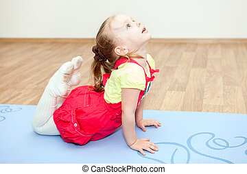 Small Caucasian girl making yoga pose on mat in gym