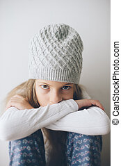 small caucasian little girl in woolen hat sitting indoors pensive in cold room