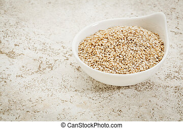 small ceramic bowl of unhulled sesame seeds against a ceramic tile background with a copy space