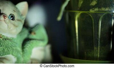 small ceramic figurine of a cat in a sweater at night -...
