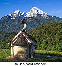 Small chapel Kirchleitn and snow-capped summits of Watzmann...