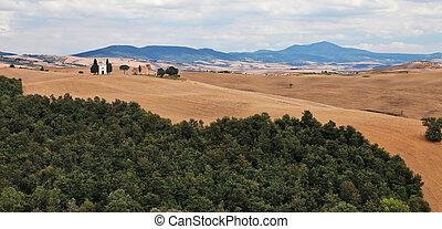 Small chapel on a hill in Tuscan farmland.