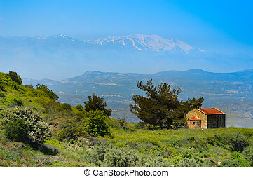 Small chapel on a hill with ida snowy mountain