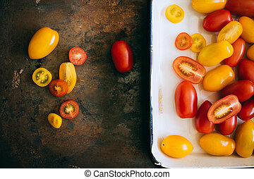 Small cherry tomatoes, red and yellow, in an enamel tray on a metal background