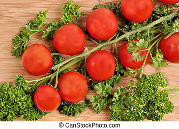 Small cherry tomatoes with parsley on a wooden background