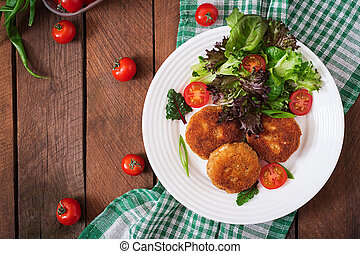 Small chicken cutlet with vegetables on a plate. Top view