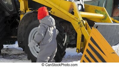 Small child approaches tractor touches wheel - Cute baby...