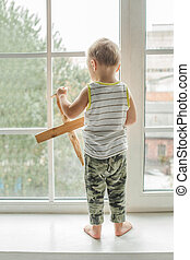 Small child boy looking out Window and Playing