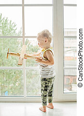 Small child boy playing with wooden plane toy and dreaming on pilots career