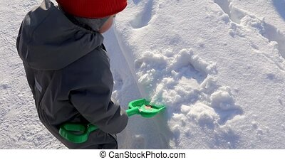 Small child collects snow green shovel - Kid trying clean...