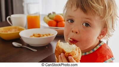 Small child eating croissant breakfast - Small child eating...