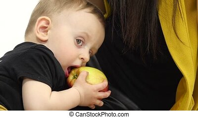 Small child eats an apple, next to her mother. White background. Slow motion. Close up