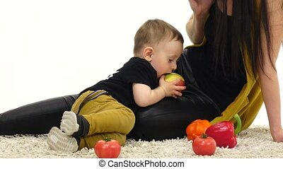 Small child eats an apple, next to her mother. White background