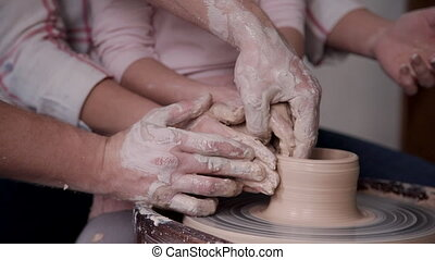 Small child girl with her charming family molding wet clay...