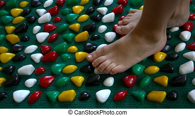 child goes barefoot on an orthopedic foot mat - small child...