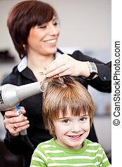Small child having a blow dray at a hairdresser