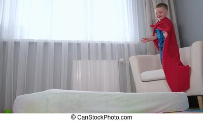 Small child in red Super man kid super hero Cape jumps from chair to mattress lying in children's room. Fall of super hero, boy's failed attempt to fly, boy's imagination. Slow motion video.
