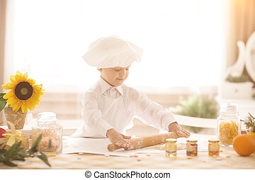 small child in the form of a cook rolls out the dough
